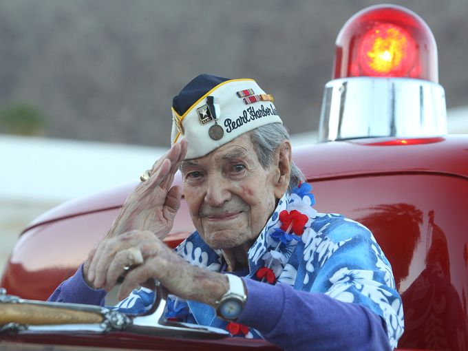 Picture of Veteran on a firetruck at Veteran's Day Parade.